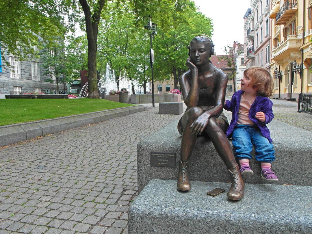 En liten jente sitter ved siden av en statue av en tenåringspike med hodetelefoner.